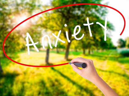 Woman Hand Writing Anxiety on blank transparent board with a marker isolated over green field background. Business concept. Stock Photo