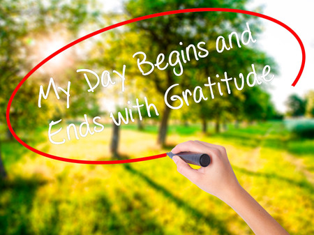 humility: Woman Hand Writing My Day Begins and Ends with Gratitude on blank transparent board with a marker isolated over green field background. Business concept. Stock Photo