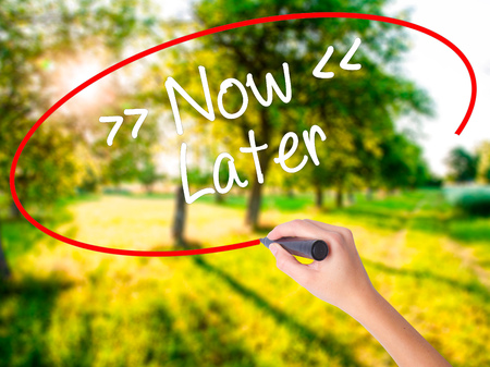 Woman Hand Writing NowLater on blank transparent board with a marker isolated over green field background. Stock Photo Stock Photo