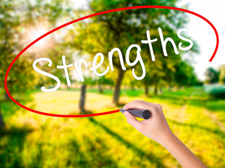 Woman Hand Writing Strengths on blank transparent board with a marker isolated over green field background. Stock Photo
