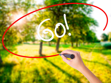 working ethic: Woman Hand Writing Go! on blank transparent board with a marker isolated over green field background. Business concept. Stock Photo
