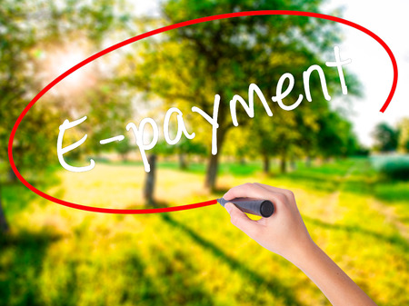 technology transaction: Woman Hand Writing E-payment on blank transparent board with a marker isolated over green field background. Business concept. Stock Photo