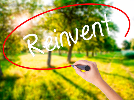 rebuilt: Woman Hand Writing  Reinvent on blank transparent board with a marker isolated over green field background. Stock Photo Stock Photo