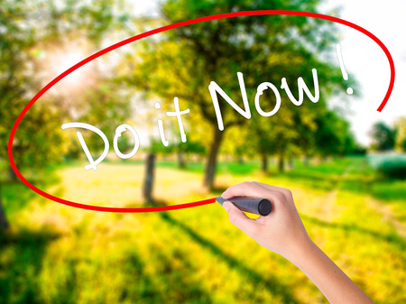 Woman Hand Writing Do it Now on blank transparent board with a marker isolated over green field background. Business concept. Stock Photo Stock Photo