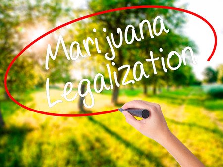 Woman Hand Writing Marijuana Legalization with a marker over transparent board . Isolated on green field. Live, technology, internet concept. Stock Photo
