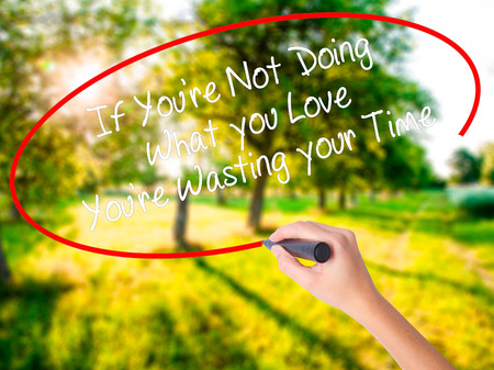 Woman Hand Writing If Youre Not Doing What you Love Youre Wasting your Time on blank transparent board with a marker isolated over green field background. Business concept. Stock Photo Stock Photo