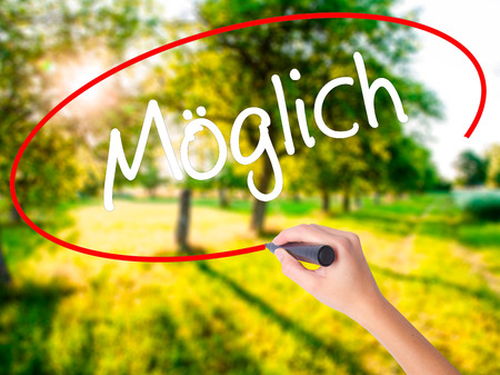 Woman Hand Writing Moglich (Possible in German) on blank transparent board with a marker isolated over green field background. Stock Photo