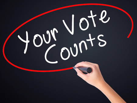presidency: Woman Hand Writing Your Vote Counts on blank transparent board with a marker isolated over black background. Business concept. Stock Photo