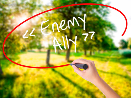 interdependence: Woman Hand Writing Enemy - Ally on blank transparent board with a marker isolated over green field background. Stock Photo Stock Photo