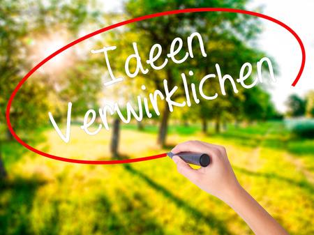 Escritura de la mano de la mujer Ideen Verwirklichen (Date cuenta de Ideas en alemán) a bordo transparente blanco con un marcador aislado sobre el fondo verde del campo. Foto de stock Foto de archivo - 63784395