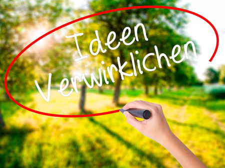 Woman Hand Writing Ideen Verwirklichen ( Realize Ideas in German) on blank transparent board with a marker isolated over green field background. Stock Photo