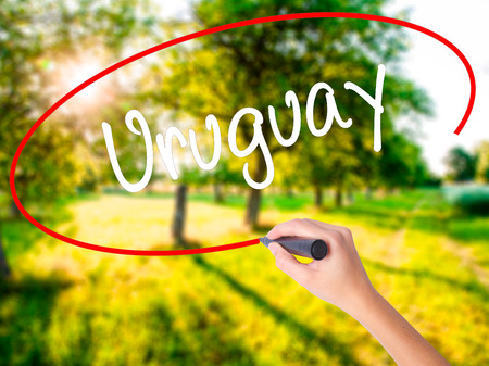 Woman Hand Writing Uruguay  on blank transparent board with a marker isolated over green field background. Stock Photo