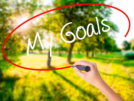 specific: Woman Hand Writing  My Goals on blank transparent board with a marker isolated over green field background. Business concept. Stock Photo