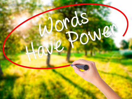 Woman Hand Writing Words Have Power on blank transparent board with a marker isolated over green field background. Business concept. Stock Photo
