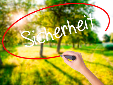 Woman Hand Writing Sicherheit (Safety in German) on blank transparent board with a marker isolated over green field background