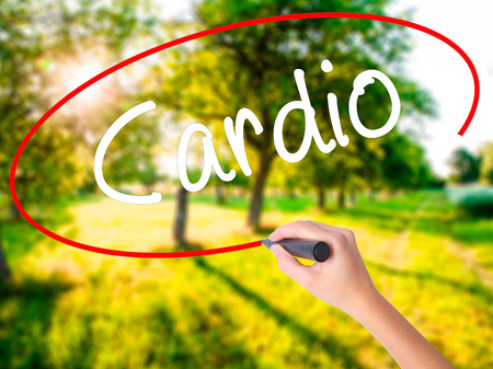Woman Hand Writing Cardio on blank transparent board with a marker isolated over green field background. Stock Photo Stock Photo