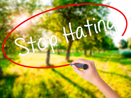 Woman Hand Writing Stop Hating  on blank transparent board with a marker isolated over green field background. Stock Photo