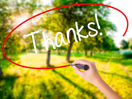 Woman Hand Writing Thanks! on blank transparent board with a marker isolated over green field background. Business concept. Stock Photo