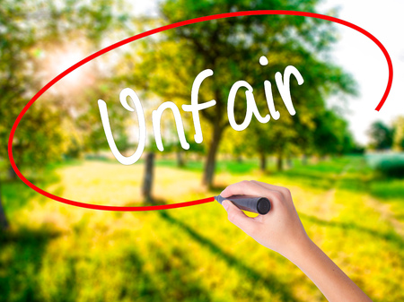 Woman Hand Writing Unfair on blank transparent board with a marker isolated over green field background. Stock Photo Stock Photo