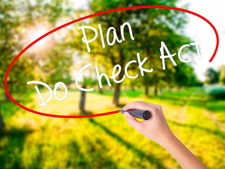 Woman Hand Writing Plan Do Check Act  on blank transparent board with a marker isolated over green field background. Business concept. Stock Photo Stock Photo