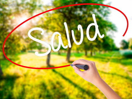 Woman Hand Writing Salud (Health in Spanish) on blank transparent board with a marker isolated over green field background. Stock Photo