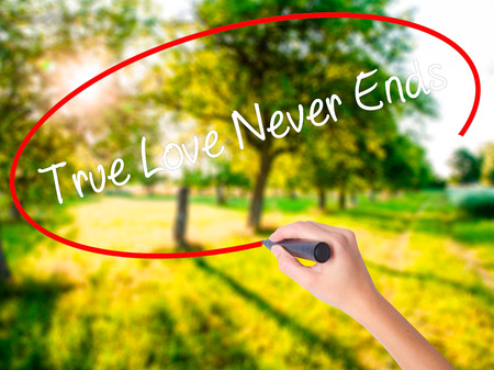 Woman Hand Writing True Love Never Ends on blank transparent board with a marker isolated over green field background. Business concept. Stock Photo