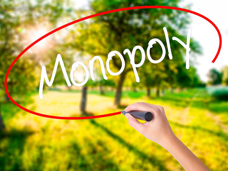 Woman Hand Writing Monopoly on blank transparent board with a marker isolated over green field background. Stock Photo