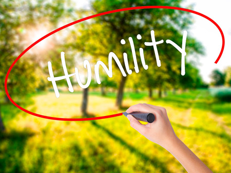 Woman Hand Writing Humility  on blank transparent board with a marker isolated over green field background. Stock Photo