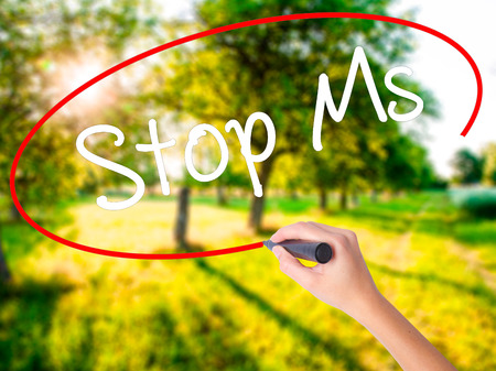 spasms: Woman Hand Writing Stop Ms on blank transparent board with a marker isolated over green field background. Business concept. Stock Photo