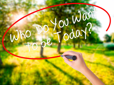 Woman Hand Writing Who Do You Want to be Today? on blank transparent board with a marker isolated over green field background. Stock Photo Stock Photo