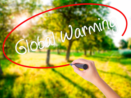 Woman Hand Writing Global Warming on blank transparent board with a marker isolated over green field background. Stock Photo