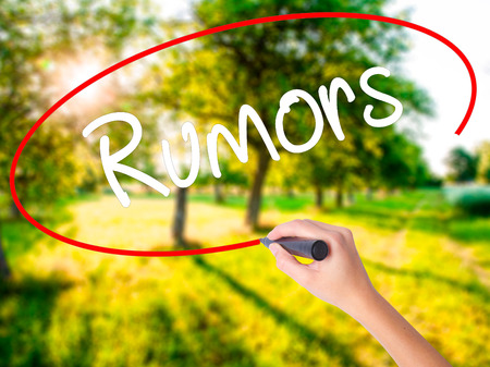 Woman Hand Writing Rumors  on blank transparent board with a marker isolated over green field background. Stock Photo Stock Photo