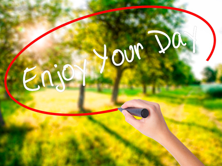 Woman Hand Writing Enjoy Your Day on blank transparent board with a marker isolated over green field background. Business concept. Stock Photo