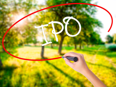 insider: Woman Hand Writing IPO (Initial Public Offering)   on blank transparent board with a marker isolated over green field background. Stock Photo