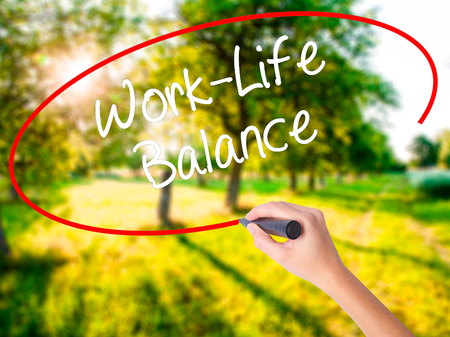 Woman Hand Writing Work-Life Balance on blank transparent board with a marker isolated over green field background. Business concept. Stock Photo