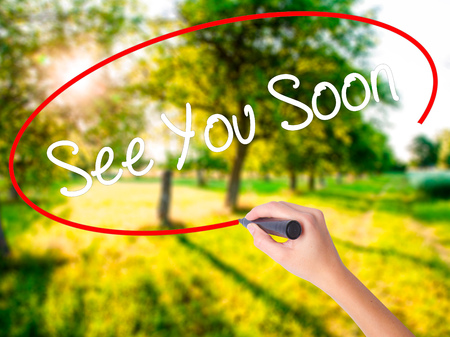 Woman Hand Writing See You Soon on blank transparent board with a marker isolated over green field background. Stock Photo