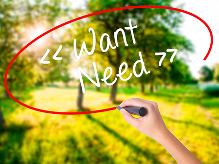 Woman Hand Writing Want - Need  on blank transparent board with a marker isolated over green field background. Stock Photo