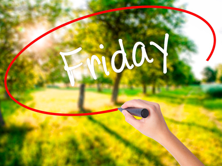 Woman Hand Writing Friday on blank transparent board with a marker isolated over green field background. Business concept. Stock Photo