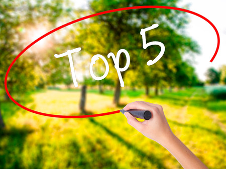 Woman Hand Writing Top 5 on blank transparent board with a marker isolated over green field background. Business concept. Stock Photo Standard-Bild