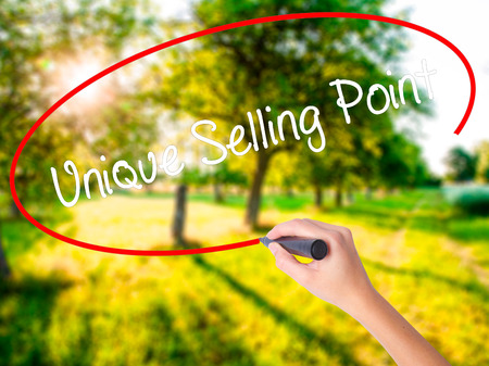 usp: Woman Hand Writing Unique Selling Point on blank transparent board with a marker isolated over green field background. Business concept. Stock Photo
