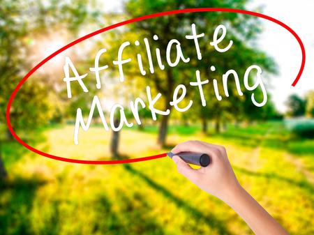 Woman Hand Writing Affiliate Marketing on blank transparent board with a marker isolated over green field background. Business concept. Stock Photo