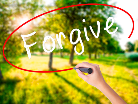 Woman Hand Writing Forgive on blank transparent board with a marker isolated over green field background. Business concept. Stock Photo
