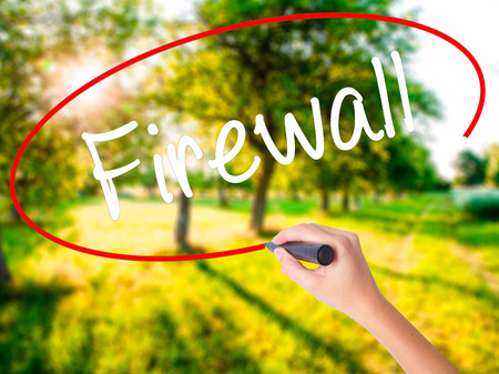 Woman Hand Writing Firewall  on blank transparent board with a marker isolated over green field background. Stock Photo