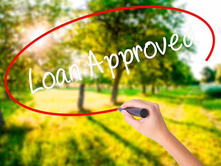 Woman Hand Writing Loan Approved on blank transparent board with a marker isolated over green field background. Business concept. Stock Photo Stock Photo