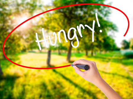 Woman Hand Writing Hungry! on blank transparent board with a marker isolated over green field background. Business concept. Stock Photo Stock Photo