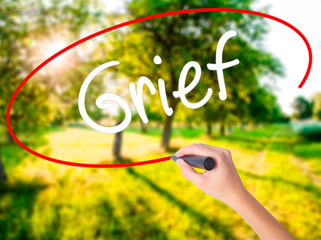 lamentation: Woman Hand Writing Grief on blank transparent board with a marker isolated over green field background. Stock Photo