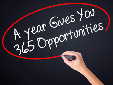 gives: Woman Hand Writing A year Gives You 365 Opportunities on blank transparent board with a marker isolated over black background. Business concept. Stock Photo Stock Photo