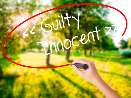 fair trial: Woman Hand Writing Guilty - Innocent on blank transparent board with a marker isolated over green field background. Stock Photo Stock Photo