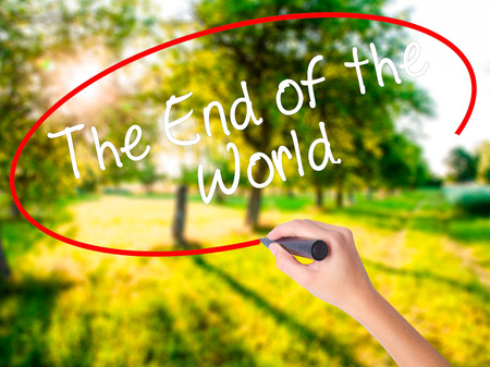 Woman Hand Writing The End of the World on blank transparent board with a marker isolated over green field background. Stock Photo