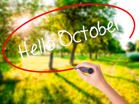Woman Hand Writing  Hello October  on blank transparent board with a marker isolated over green field background. Business concept. Stock Photo Stock Photo
